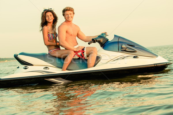 Multi ethnic couple sitting on a jet ski Stock photo © Nejron