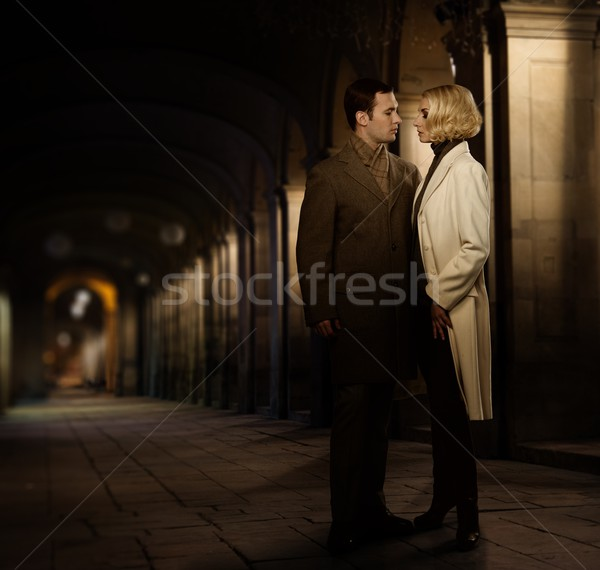 Elegant couple in autumnal coats standing outdoors at night Stock photo © Nejron