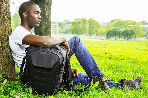 Young african american man in white shirt  with rucksack in a park Stock photo © Nejron