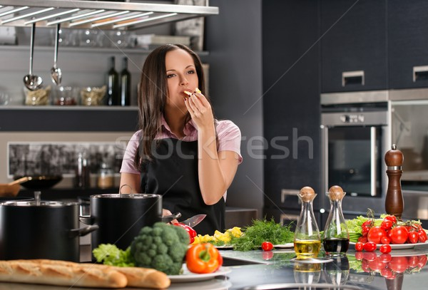 Stock photo: Happy young woman in apron on modern kitchen tasting food while cooking