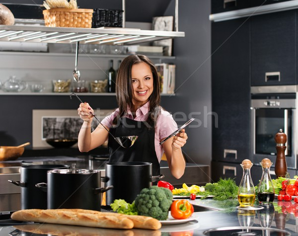 Cheerful young woman in apron on modern kitchen with ladle and pot Stock photo © Nejron