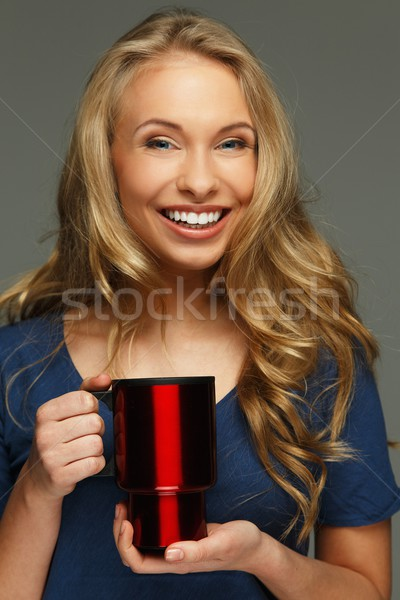 Positive young woman with long hair and blue eyes holding thermo mug Stock photo © Nejron
