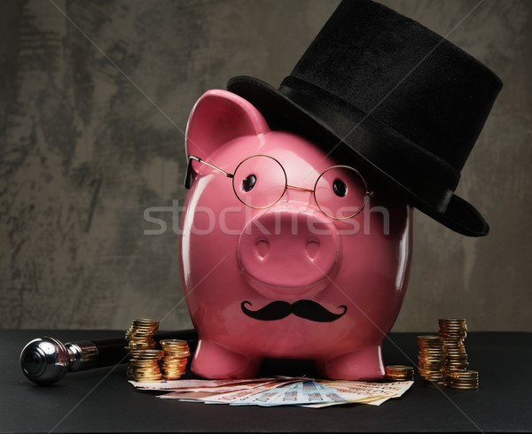 Piggybank in glasses and hat with pile of coins and banknotes  Stock photo © Nejron