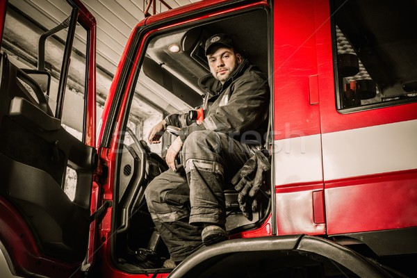 Fireman behind steering wheel of a firefighting truck  Stock photo © Nejron
