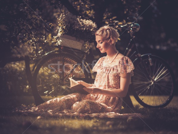 Blond retro woman with a book in summer dress sitting on a meadow Stock photo © Nejron