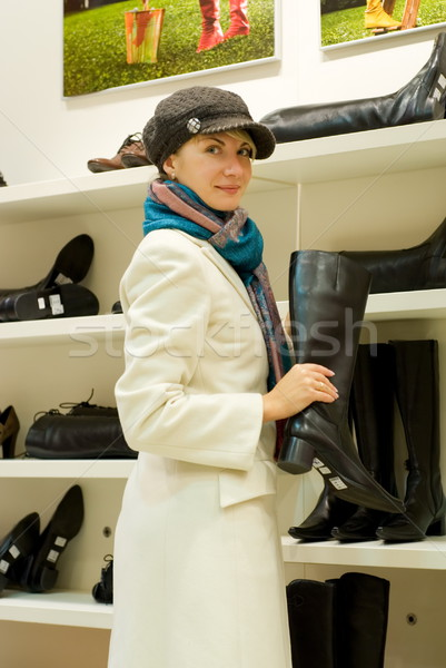Beautiful girl in a shop buying winter boots Stock photo © Nejron