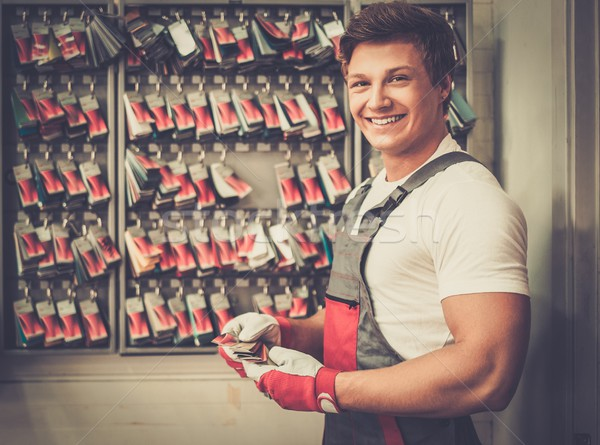 Cheerful serviceman near stand with colour samples in car body workshop Stock photo © Nejron