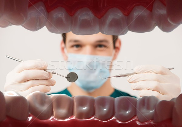 View at young male dentist holding dental tools from patient mouth  Stock photo © Nejron
