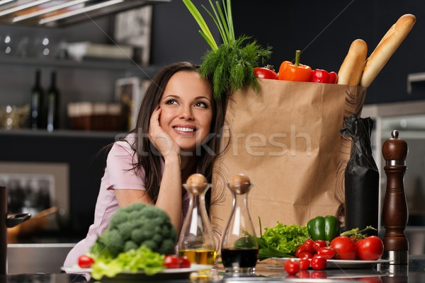 Young woman with grocery bag full of fresh vegetables on a modern kitchen Stock photo © Nejron