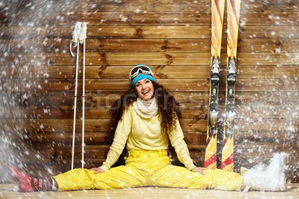 Happy woman with skis and ski boots sitting near wooden wall in snowflakes Stock photo © Nejron