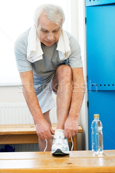 Senior man tying up sneakers in fitness club locker room Stock photo © Nejron