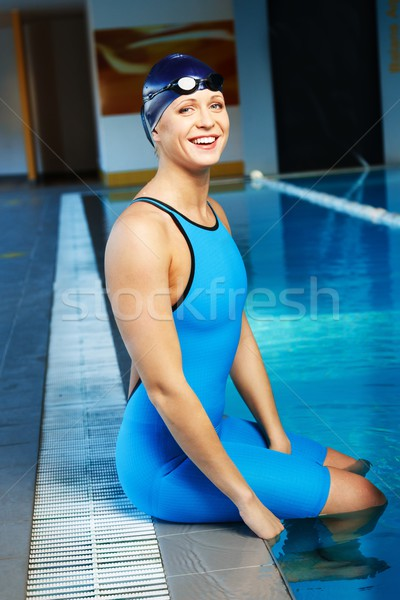 Young woman wearing blue swimming suit and hat in swimming pool  Stock photo © Nejron