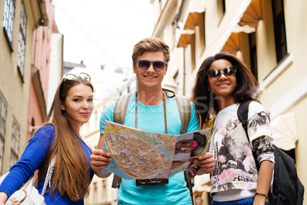 Stock photo: Multi ethnic friends tourists with map in old city