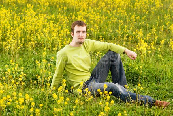Jeune homme séance champ de fleurs Photo stock © Nejron