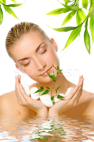 Beautiful woman holding young plant growing up through stones re Stock photo © Nejron