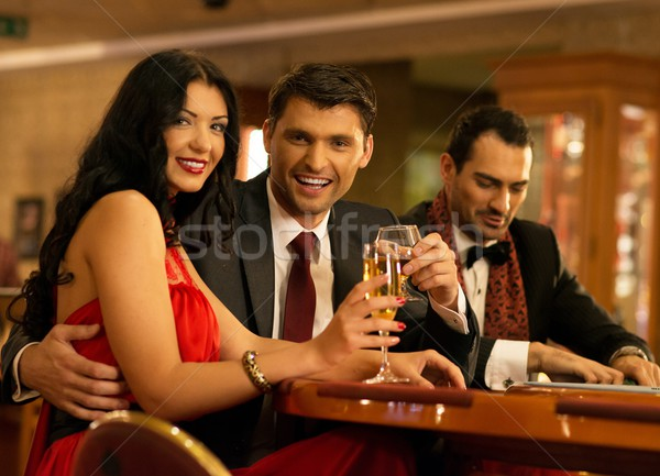 Happy young people behind gambling table with drinks Stock photo © Nejron