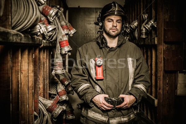 Stock photo: Firefighter in storage room with fire hoses