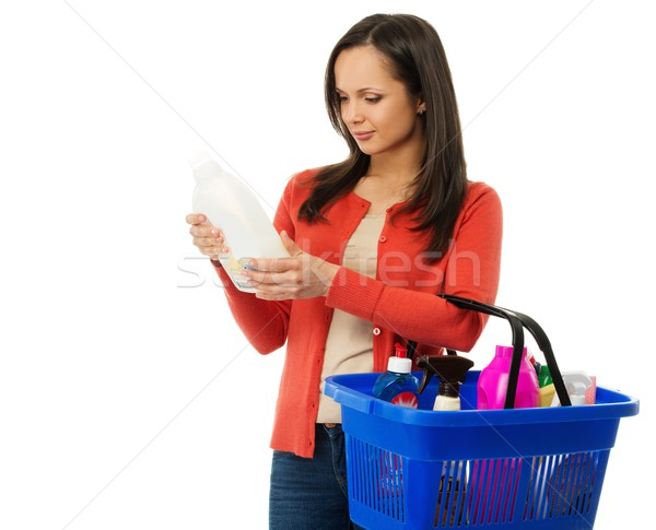 Beautiful brunette woman with basket reading label on cleanser  Stock photo © Nejron