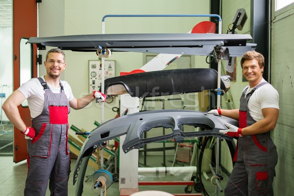 Two workers with car bodykit ready for painting in a workshop Stock photo © Nejron