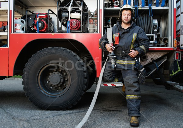 Stock photo: Firefighter near truck with equipment with water water hose over shoulder