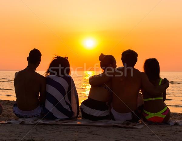 Sylwetki młodych ludzi posiedzenia plaży patrząc wygaśnięcia Zdjęcia stock © Nejron