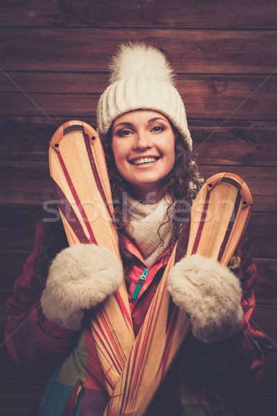 Smiling woman with skis standing against wooden house wall  Stock photo © Nejron