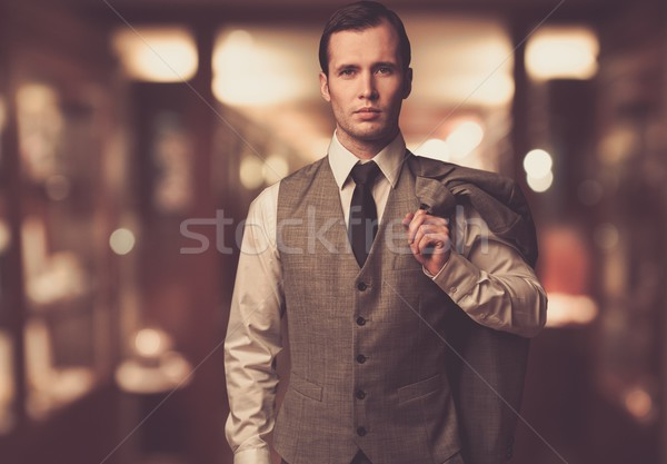 Man in waistcoat with jacket over his shoulder against blurred background Stock photo © Nejron