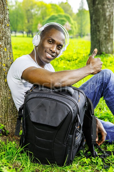 Smiling young african american man in white shirt listens music in a park Stock photo © Nejron