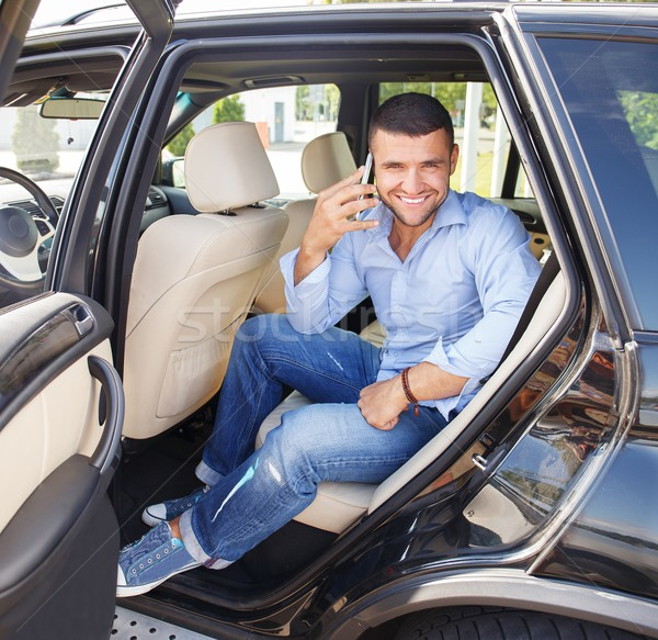 Handsome stylish man on a back seat with a mobile phone Stock photo © Nejron
