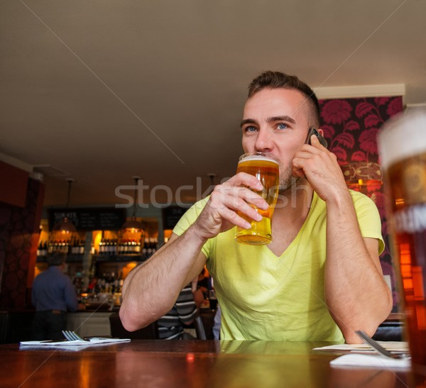 Handsome young man with mobile phone and beer in a pub Stock photo © Nejron