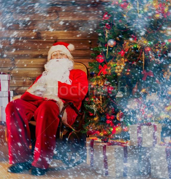 Święty mikołaj posiedzenia bujane domu wnętrza Zdjęcia stock © Nejron