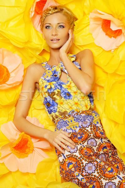 Beautiful young blond woman in colourful dress lying among big yellow flowers Stock photo © Nejron