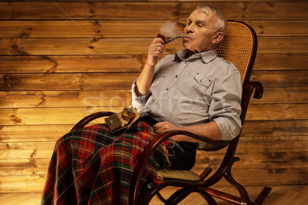 https://img3.stockfresh.com/files/n/nejron/m/80/4343817_stock-photo-senior-man-with-smoking-pipe-sitting-on-rocking-chair-in-homely-wooden-interior.jpg