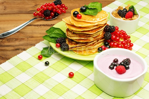 Healthy breakfast with pancakes, fresh berries and yoghurt on tablecloth in rural interior  Stock photo © Nejron