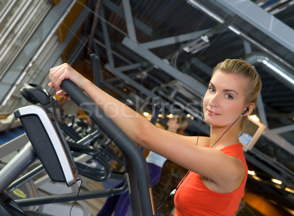 Stock photo: Beautiful young woman doing exercise in a gym while listening to