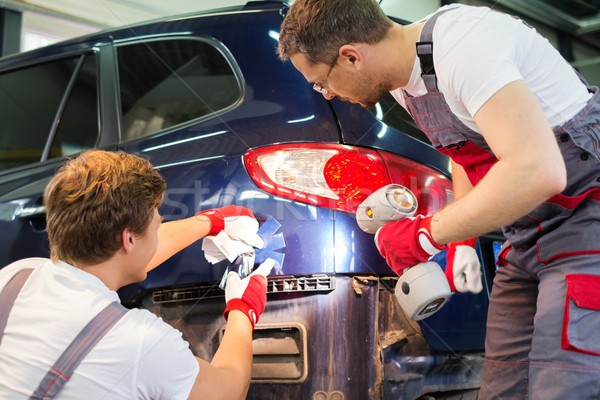 Two workers with colour samples choosing correct shade in a car body workshop  Stock photo © Nejron