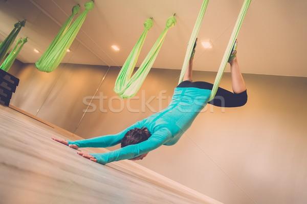 Young woman performing antigravity yoga exercise  Stock photo © Nejron