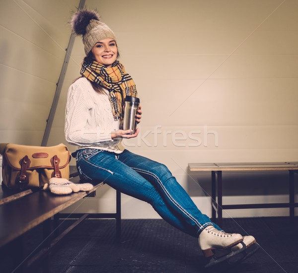 Cheerful girl with mug of hot drink in ice rink locker room  Stock photo © Nejron