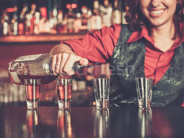 Beautiful redhead barmaid making shots Stock photo © Nejron