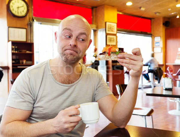Middle-aged man enjoying coffee with a pintxo in a cafe Stock photo © Nejron