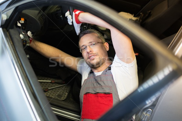 Cheerful mechanic with wrench fixing something in a car interior  Stock photo © Nejron
