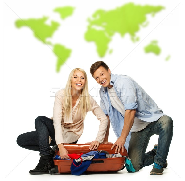 Young couple packing suitcase for a journey against world map Stock photo © Nejron