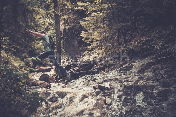 Hombre caminante saltar corriente montana forestales Foto stock © Nejron