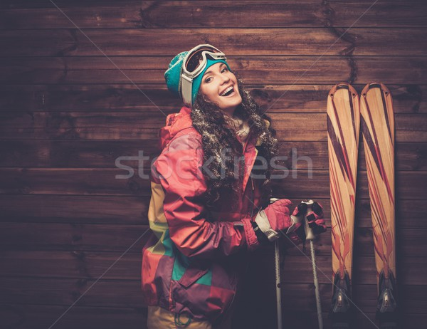 Smiling woman with skis and poles standing against wooden house wall  Stock photo © Nejron