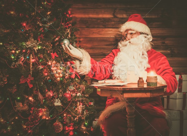 Santa Claus in wooden home interior looking at decorated Christmas tree Stock photo © Nejron