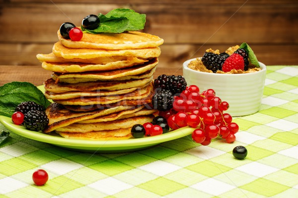 Healthy breakfast with pancakes, fresh berries and muesli on tablecloth in rural interior  Stock photo © Nejron
