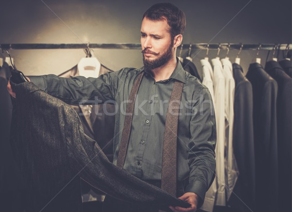 Handsome man with beard choosing jacket in a shop Stock photo © Nejron