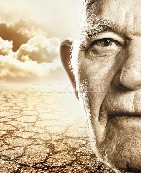 Elderly man's face over dry desert land background Stock photo © Nejron