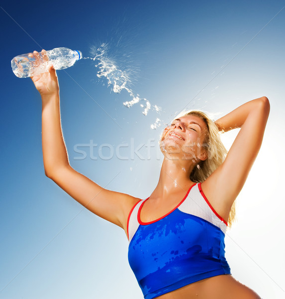 Young woman drinking water after fitness exercise Stock photo © Nejron