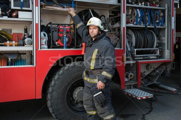 Fireman taking equipment from firefighting truck  Stock photo © Nejron